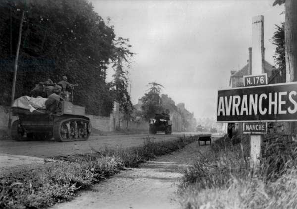U.S. light tanks passing a road sign for the town of Avranches, southeast of the Falaise Pocket. In the early days of Operation Cobra, the First U.S. Army's battle against Germans' Operation Luttich in Normandy. August 1-2, 1944. France, World War 2