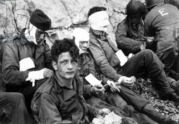 U.S. assault troops of the 16th Infantry Regiment, wounded on Omaha Beach, on D-Day. They wait for evacuation for further medical treatment. Collville-sur-Mer, Normandy, France, June 6, 1944, World War 2