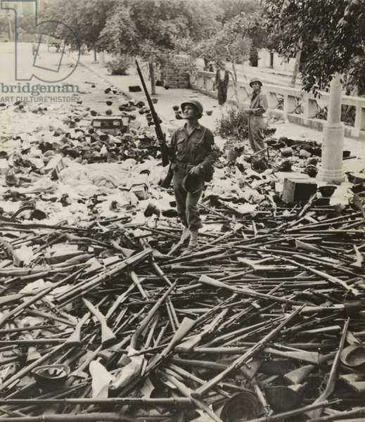 American M.P. standing on a large pile of Italian weapons on a street in Palermo, Italy, on August 6, 1943. Palermo, a strategic port, fell on July 20, only 10 days after the Allied invasion of Sicily