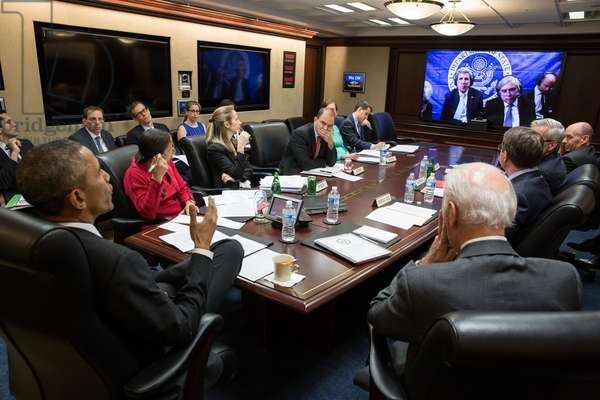 President Obama and National Security team in teleconference on the P5+1 negotiations with Iran. March 31, 2015. On the screen are Sec. of State John Kerry, Sec. of Energy Ernest Moniz and the U.S. negotiating team in Lausanne, Switzerland. Susan Rice, National Security Advisor wears a red sweater