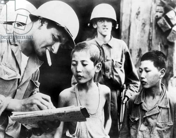 SOMEWHERE IN KOREA, 10/6/50: Two North Korean boys, serving in North Korean Army, are interrogated by a GI after their capture.