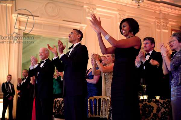 President and Michelle Obama applaud Harry Connick Jr. and the Big Band during the Governors Ball at the White House. Michelle wears a black georgette tiered ruffle gown by Thakoon and sparkling bangle bracelets. Feb. 21 2010.,