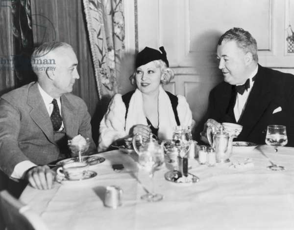 Mae West dining at the Victor Hugo Café with her manager James Timony (right). At left is John Hammel of New York. 1933