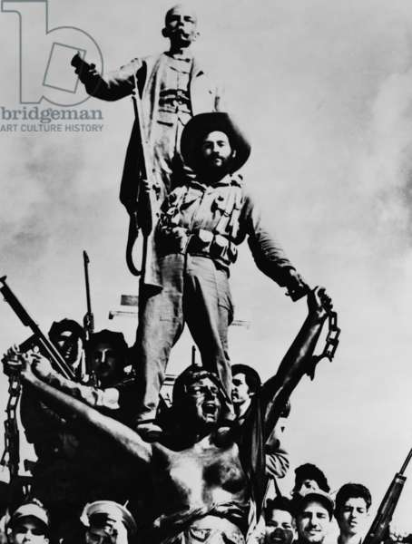 Cuban Revolutionary soldiers celebrating victory on a monument in Matanzas, Cuba. Sculptures are of Cuban national hero, Jose Marti, and allegorical figure of liberty breaking chains, February 1959