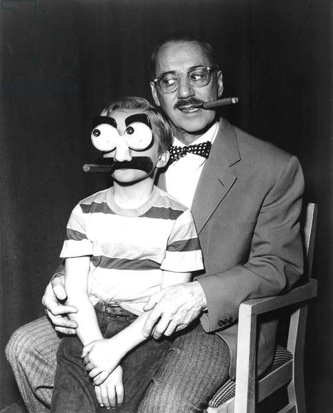 Groucho Marx and a child with a Groucho mask, 1955