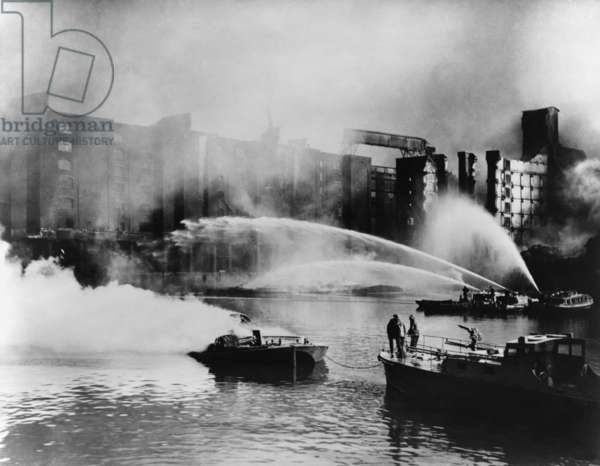 London Firemen direct water from their fireboats onto blazing warehouse. The Germans bombed the port facilities on the London waterfront. 1940, during the Battle of Britain, World War 2