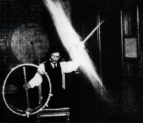 Nikola Tesla 1856-1943 conducted spectacular demonstrations of electricity. This image published in ELECTRICAL REVIEW in 1899 was accompanied by with this caption The operator's body in this experiment is charged to a high potential by means of a coil responsive to the waves transmitted to it from a distant oscillator