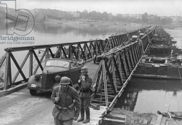 German army invades of Poland. Vehicles pass over a bridge constructed by German Army engineers crossing the Vistula River near Bydgoszcz, Poland. In the left distance is a destroyed bridge. World War 2. Sept. 16, 1939