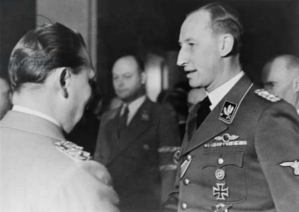 Reinhard Heydrich speaking with Hermann Goering at Goering's birthday celebration, Jan. 12, 1942. In this same month, January 1942, Heydrich chaired the Wannsee Conference, which planned the 'final solution' for the deportation and extermination of all Jews in German-occupied territory during World War 2