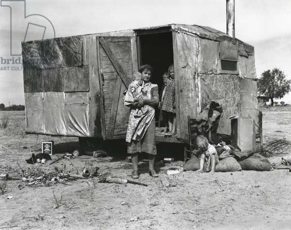A migratory family living in a trailer in an open field, Arizona, November 1940 (b/w photo)