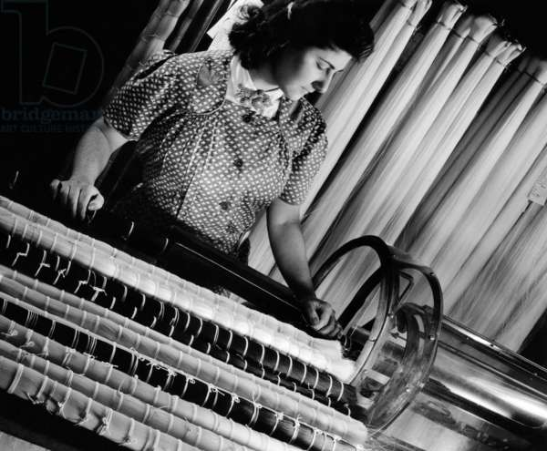 DuPont operator manufacturing nylon products. She is tying nylon hanks in preparation for cutting the filament into short bristle length bundles. These will be used for bristles in tooth and hair brushes. c. Mid 1940s