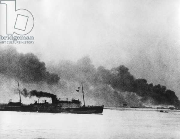 Ship leaving Dunkirk carrying defeated British and French soldiers to England. In the background the French port of Dunkirk burns under the German advance. World War 2. May 26-June 4, 1940