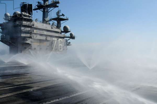 Sprinklers spray the flight deck of the USS Ronald Reagan after radioactive fallout from tsunami damaged nuclear power plants. March 23 2011.,
