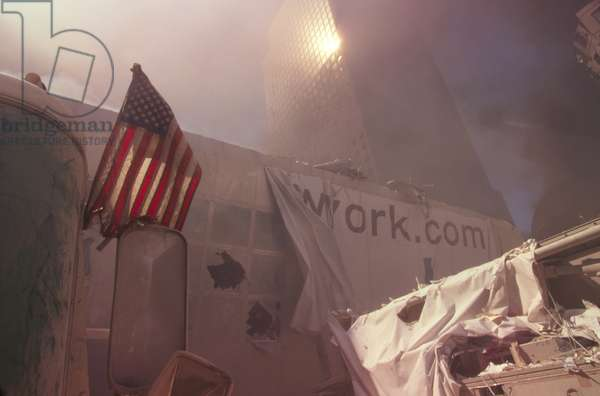 American flag planted in the rubble of World Trade Center after 9-11 terrorist attacks. The nearest structure is a pedestrian bridge over the West Side Highway (West St.) that connected the WTC with the World Financial Center. New York City, Sept. 11, 2001. In the background is WFC 2