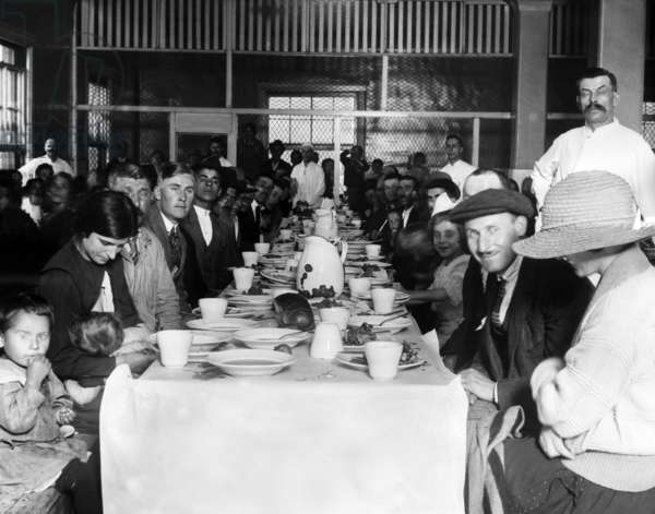 Immigrants who are awaiting approval of their entry into the U.S. crowd in the lunchroom for their noonday meal. Ellis Island, New York. c. 1923
