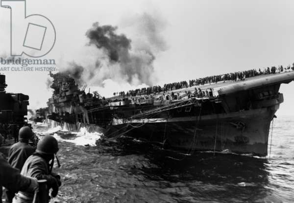 USS Franklin aircraft carrier on fire and listing after a strike by a Japanese dive bomber. USS Santa Fe (at left) assists the crippled carrier, that suffered 800 crewmen killed. March 19, 1945. World War 2, Pacific Ocean