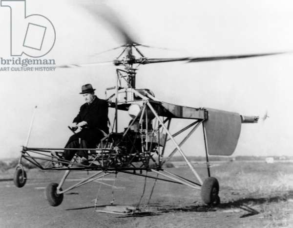 Igor Sikorsky at the controls of the VS-300 helicopter. It lifts off the ground on one of its early test flights in Sep. 1939. Weights were hung from the landing gear struts to prevent it from rising to as the controls are tested