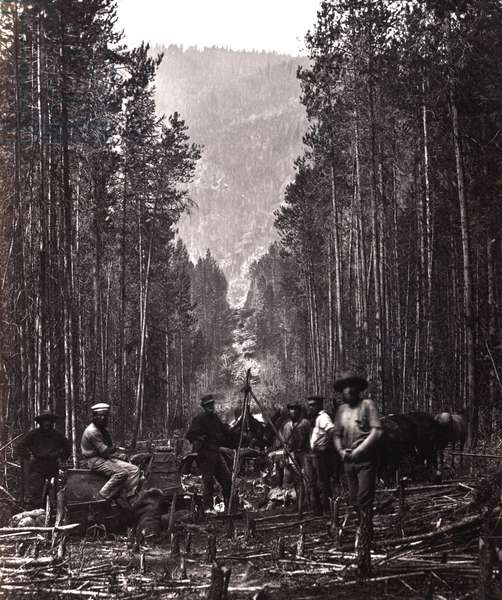Cutting the boundary line. Men of the British North American Boundary Commission survey crew posed in clearing, with transit, marking the boundary line between Canada and the United States, along the right bank of the Moyie River, Idaho. c. 1860