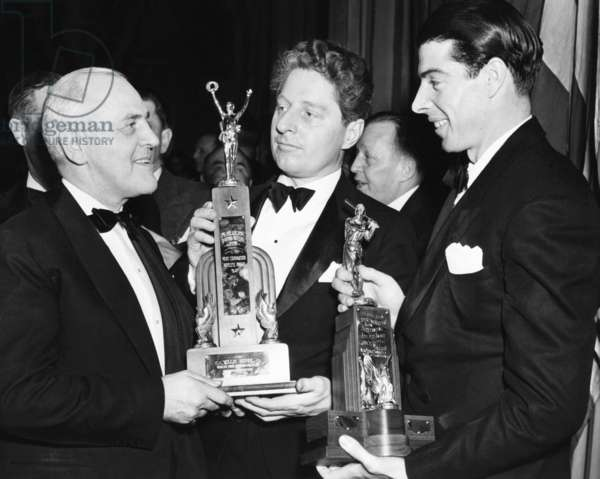 Billiards Champion, Willie Hoppe, receives a trophy as the 'Most Courageous Athlete of 1941.' With pneumonia, he rose from sick-bed to defend his title by winning over Jake Schaefer. At right is Joe DiMaggio, Yankee outfielder, with his trophy as the 'Nation's Outstanding Athlete.' Jan. 30, 1942. At left is Cy Peterson, President of the Philadelphia Sporting Writers Association