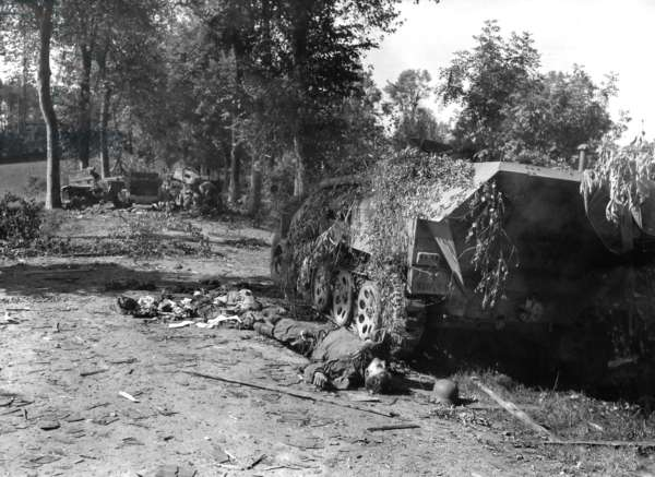 Dead German soldier lies beside a wrecked half-track near Mortain. This was the farthest reach of the German counter attack, Operation Luttich, during the Battle of the Falaise Pocket. August 6-12, 1944, in Normandy, France, World War 2