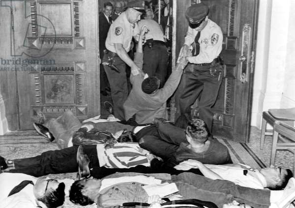 Demonstators removed by police in Sacramento, CA 6/14/63. CORE sponsored lie-in for fair housing bill.