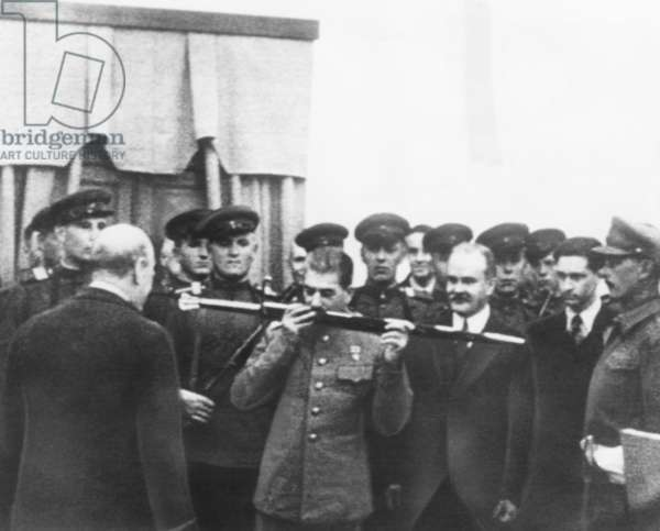 Josef Stalin kisses sword given by British in honor of the citizens of Stalingrad. Dec. 7, 1943. Winston Churchill (back to camera), made the presentation. Molotov, is on Stalin's left