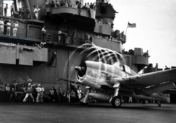 Motion of its propellers causes an 'aura' to form around this F6F Hellcat fighter on USS YORKTOWN. Nov. 1943. World War 2, Pacific Ocean