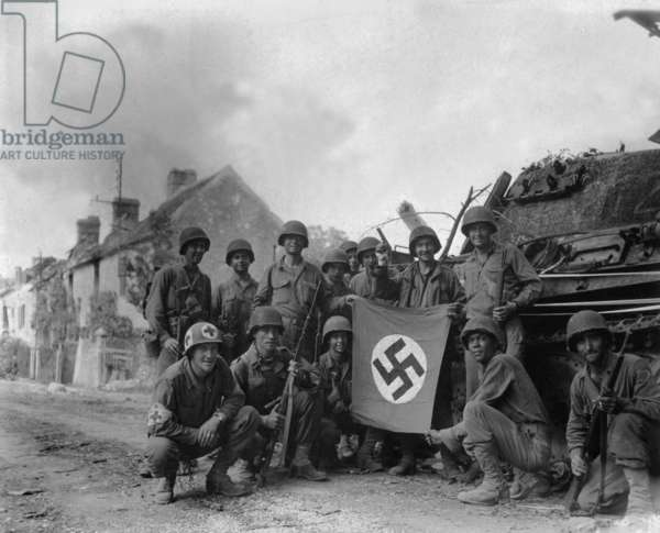 U.S. Soldiers display a captured swastika flag on August 20, 1944. Two days after the Battle of the Falaise Pocket, they were left behind to 'mop-up' in Chambois. Normandy, France, World War 2
