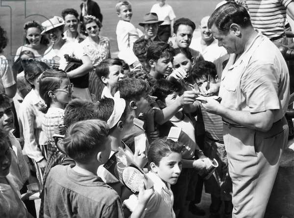 New York Yankees. Right: Retired outfielder Babe Ruth, signing autographs, c.early 1940s