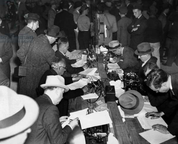 First reports of the Hindenburg disaster. Newspaper men and telegraph operators work together in the pressroom of Lakehurst Naval Air Station to report the Hindenburg disaster. May 6, 1937