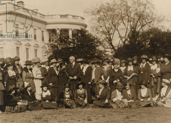 National Woman's Party members with President Harding on the lawn in front of the White House. The women ask the president's aid in passing an 'Equal Rights Bill' in the next Congress. The bill they proposed would give married women citizenship and equal rights of inheritance and contract