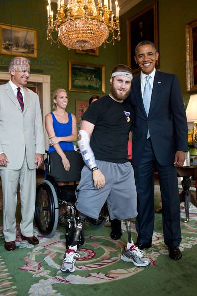 Petty Officer Taylor Morris was presented with a Purple Heart by Pres. Barack Obama. Morris also received a Bronze Star for valorous conduct. A quadruple amputee wounded in Afghanistan, he is fitted with prosthetics that allow him to walk and a motorized hand. Green Room of the White House, July 26, 2012