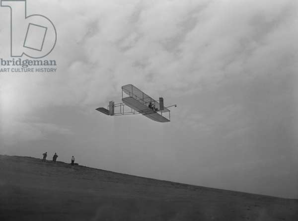 Wilbur Wright pilots a glider during Wright Brothers' flight experiments at Kitty Hawk, North Carolina. c. 1902