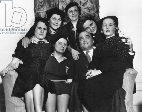 FBI Director J. Edgar Hoover on a loveseat with six women at the Willard Hotel, Washington, D.C. They were attending the convention of the International Association for Identification, for professionals in forensic identification, investigation, and scientific examination of physical evidence. c. 1940