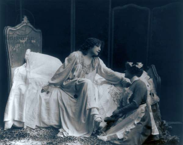 Sarah Bernhardt (1844-1923), French actress, in the role of the dying Camille, with her maid helping her put on her slippers. c. 1887
