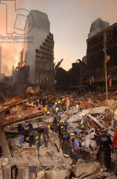 Firefighters and search and rescue teams work on 'The Pile' of rubble from the collapsed World Trade Center. In back ground is one of the buildings of the damaged World Financial Center. Sept. 16 2001
