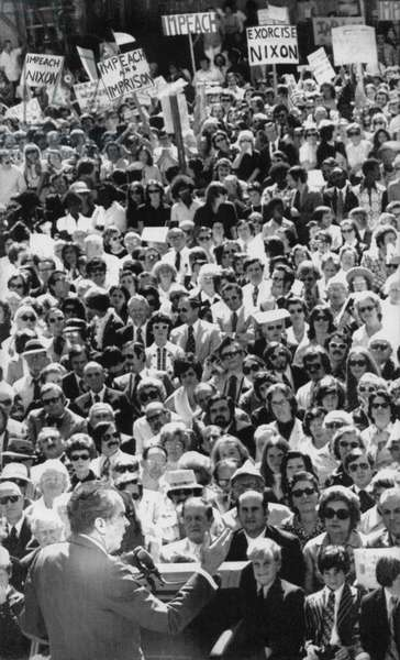 Nixon Presidency. US President Richard Nixon addresses a group of supporters, with protesters at rear of crowd, c.1970s