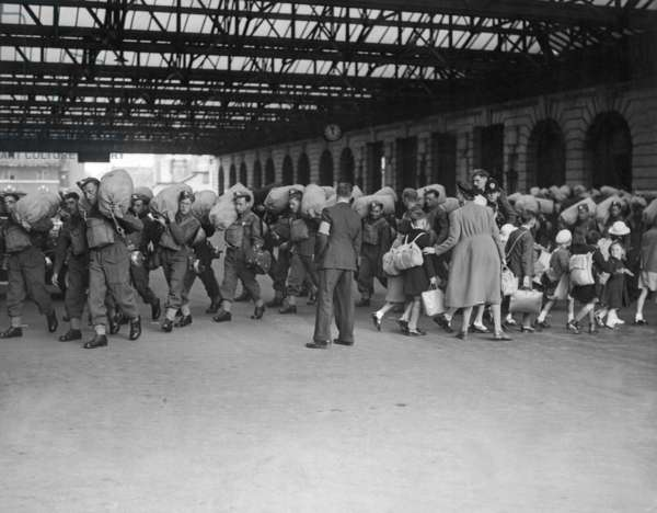 World War 2, Battle of Britain. Going in opposite directions, troops arrive in a London railroad station, as children are evacuated to the safer countryside. c. 1940