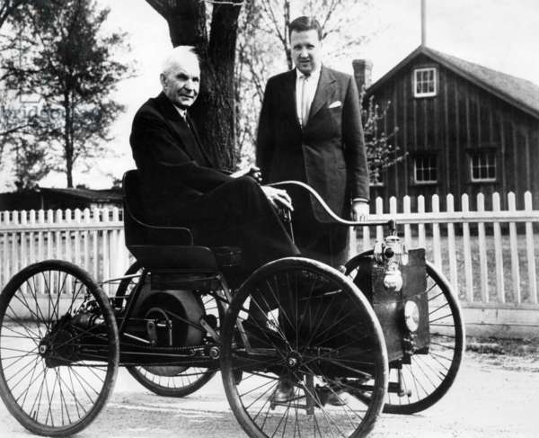 Henry Ford sits in his first Ford car built in 1896, as his grandson, Henry Ford II stands nearby. c. 1946