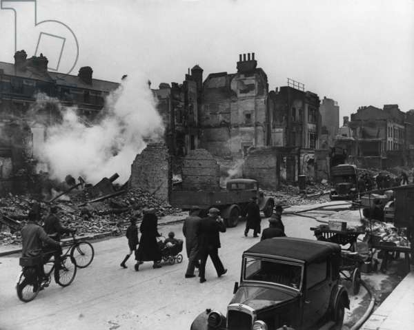 World War 2, Battle of Britain. Londoners walk through a ruined street with their bicycles and a baby carriage during the Blitz. c. 1940-41