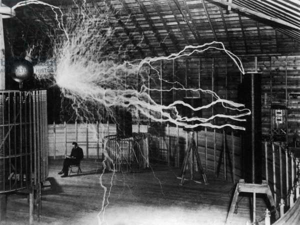 Nikola Tesla 1856-1943 created a double exposure photograph of himself reading undisturbed by a 22 foot long discharge of artificial lightning of millions of volts of electricity