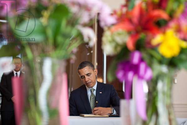 President Obama signs a condolence book for Japan's tsunami victims at the Japanese Embassy. Standing at left is Japanese Ambassador Ichiro Fujisaki. March 17 2011. (BSWH_2011_8_145)