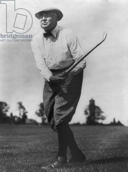 President Warren G. Harding (1865-1923), swinging golf club
