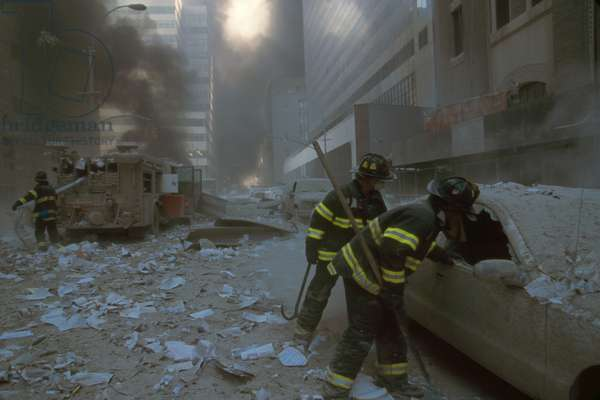 NYC firemen checking a car on Barclay Street after the 9-11 terrorist attack on World Trade Center. In the mid-ground fireman pulls a water hose from fire truck. View is toward West Broadway and includes WTC 7, on right, clad in red exterior masonry. WTC 7 collapsed at 5:20 PM on Sept. 11, 2001, due to fires ignited by debris from the North Tower (WTC 1) destruction earlier in the day