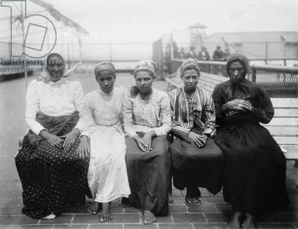 Barefoot women immigrants at Ellis Island are from the Caribbean. c. 1910