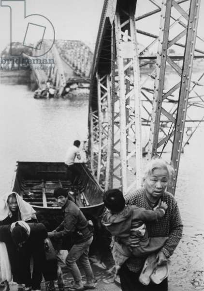 Refugees flee Tet Offensive in Hue. Refugees use a rope ferry to escape to the south shore of the Perfume River despite the destroyed bridge. c. February 1968