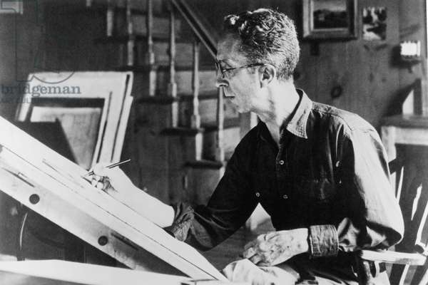 Norman Rockwell (1894-1978), American painter, at his drawing board, c.1940s