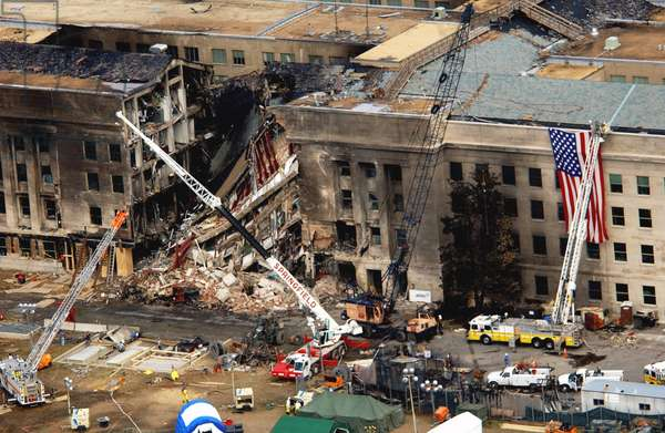 The Pentagon showing the impact point two days after a hijacked American Airlines Flight 77 was crashed into the building on Sept. 11 2001. The huge 20 x 38 feet American flag is visible to the right of the damaged area, Photo by:Everett Collection