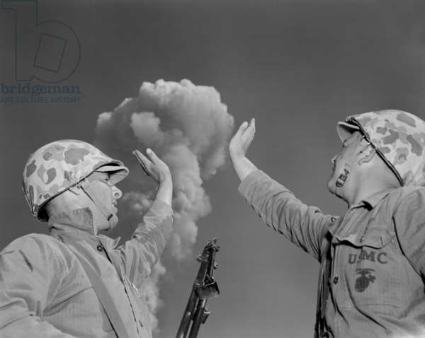 Soldiers pose below an atomic cloud at the Nevada Proving Ground. Soldiers conducted maneuvers in the vicinity of nuclear tests in 1951