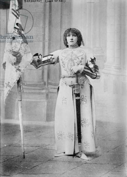 Sarah Bernhardt (1844-1923), French actress, dressed in costume as Joan of Arc, holding a flag, 1900